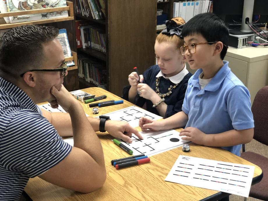 Faith Christian Academy teacher works with two elementary students.
